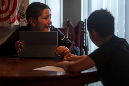 """Brothers Sami, 8, and Amjad, 10, Adham gather at the dining room table as the """"school day"""" starts around 9 a.m. at their home in Salem on April 23, 2020. Sami has autism and tends to focus on schoolwork in short bursts."""