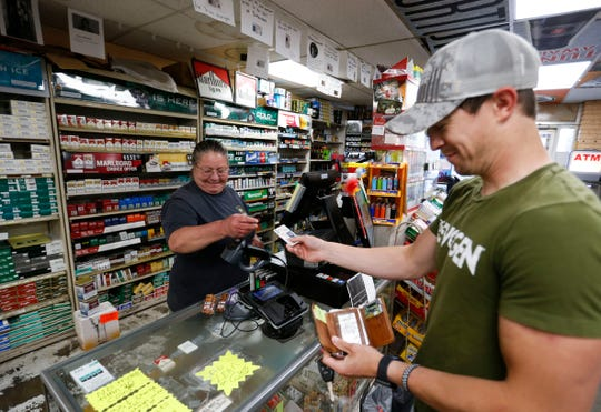Discount Smokes and Beer employee Trudy Roberson checks Jace Glover's ID as he buys vaping supplies on Thursday, April 23, 2020.