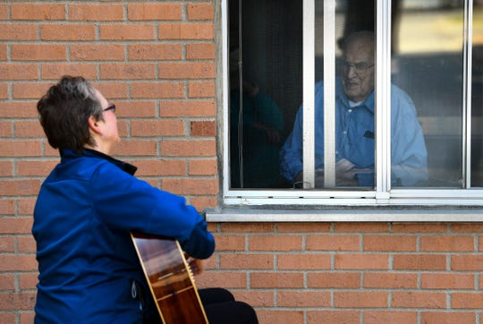 """Music therapist Rachel Amberson sings """"Edelweiss"""" while observing social distancing guidelines through an open window with St. Benedict's Community resident Joe Feneis Wednesday, April 22, 2020, in St. Cloud."""