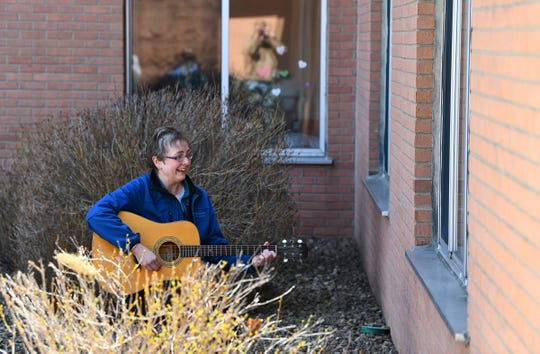 Music therapist Rachel Amberson works with a resident at St. Benedict's Community through an open window Wednesday, April 22, 2020, in St. Cloud.