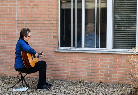 Music therapist Rachel Amberson joins St. Benedict's Community resident Joe Feneis in a song through an open window Wednesday, April 22, 2020, in St. Cloud.