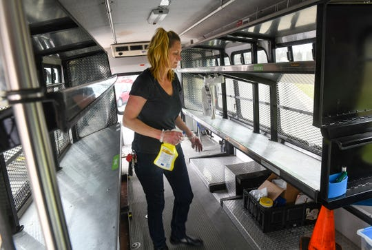 Nicole Kissner sanitizes shelves on the mobile food pantry after making deliveries Thursday, April 23, 2020, at Catholic Charities in St. Cloud.