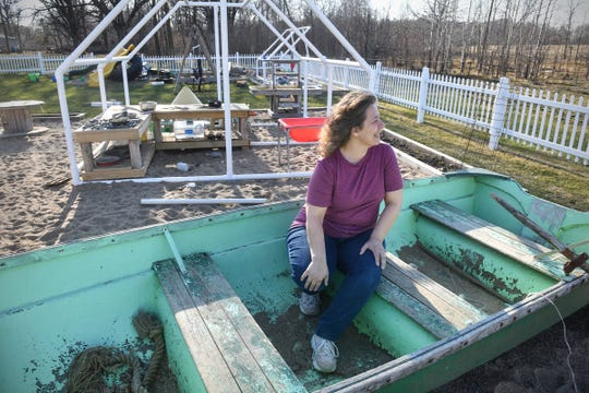 BarbaraLee Malikowski sits in a boat that is popular part of the play area at her business, 40 Acres Childcare, Wednesday, April 22, 2020, at 40 Acres Childcare near Foley.