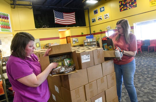 Michelle Callahan, left, and Julie Reberg Display boxes of emergency food items Thursday, April 23, 2020, at Catholic Charities in St. Cloud.