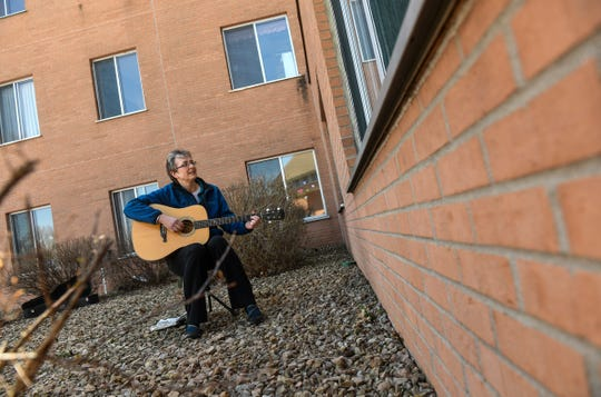 Music therapist Rachel Amberson sings with a resident through an open window Wednesday, April 22, 2020, at St. Benedict's Community in St. Cloud.