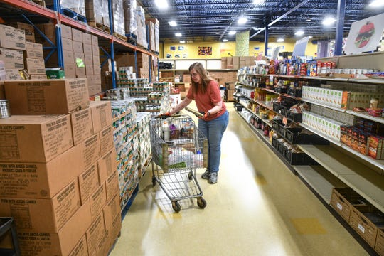 Julie Reberg fills a cart with food Thursday, April 23, 2020, at Catholic Charities in St. Cloud.