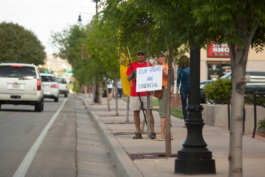 Washington County residents carry signs along St. George Boulevard to protest quarantine orders in relation to COVID-19 Wednesday, April 22, 2020.