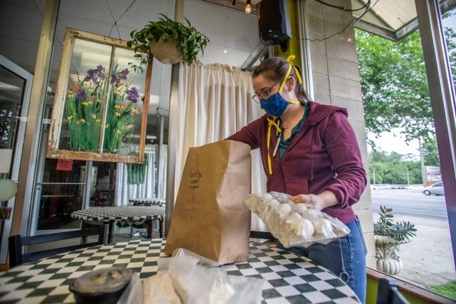 Uptown Cafe manager Katie Callis bags grocery items for a customer. Uptown Cafe among several other Tallahassee restaurants are selling basic groceries as another service for customers.