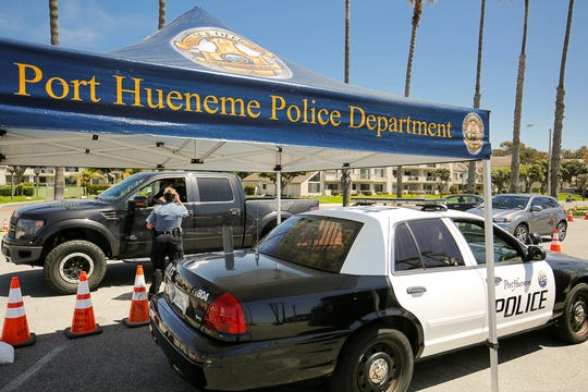 Port Hueneme police have set up a greeting checkpoint at Hueneme Beach to remind visitors of social distancing requirements during the COVID-19 pandemic.