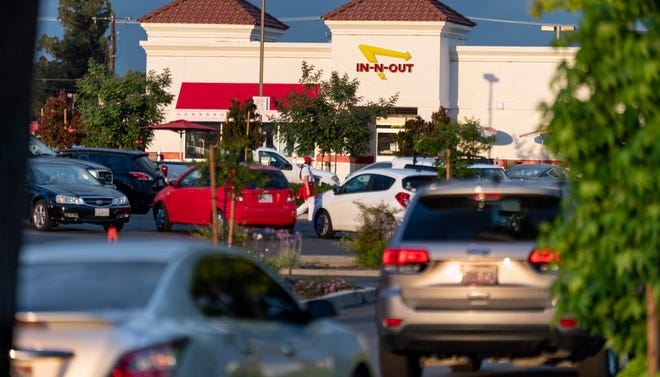 The drive-thru line for In-n-Out Burger is even longer than usual, reaching into the Ace Hardware parking lot on Monday, April 20, 2020.