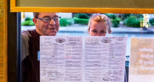 Tracy Hickam and his daughter Kimberly Hickam of Visalia browse the to-go menu in the window of Brewbakers on Monday, April 20, 2020.