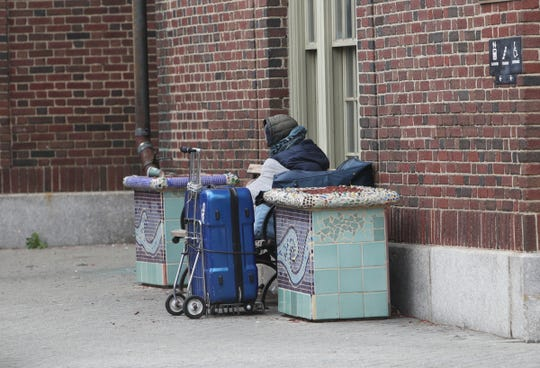 A man with a suitcase sits outside the Yonkers train station on Thursday, April 23, 2020.