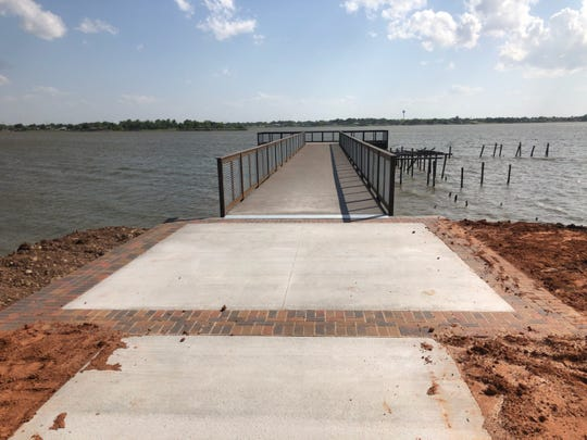 A concrete walkway lined with brick is seen Wednesday at the entrance to the newly constructed boardwalk at Lake Wichita.
