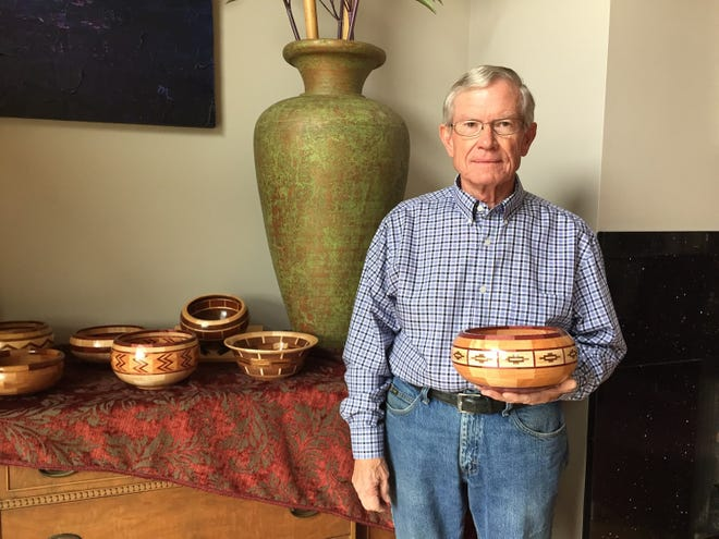 Retired doctor Mike Knell holds a bowl he turned on his lathe.