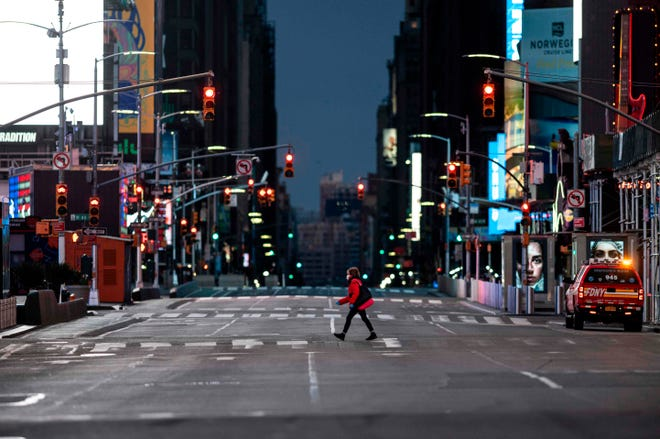A woman walks through an almost-deserted Times Square on April 23 in New York City.