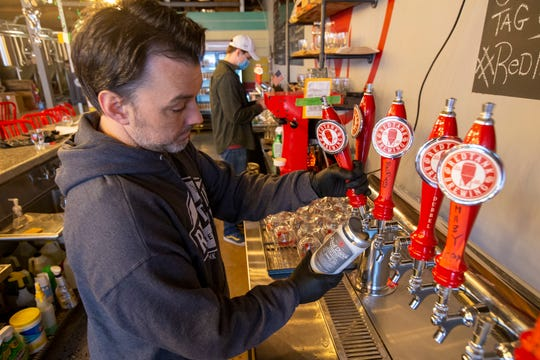 John Arcara, owner of Red Tank Brewing Company, fills a crowler with beer in Red Bank, NJ Friday, April 24, 2020. The brewery's tap room has closed but they are still distributing in eight counties and serving customers takeout orders.