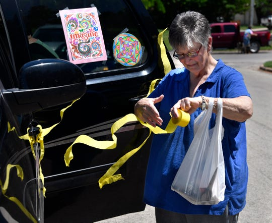 Janis Clements unwinds yellow bunting as she and her daughter Jana Allen decorate their vehicle Friday. Clements' husband Elden, known by all as Junior, is a resident of The Oaks at Radford Hills Healthcare Center, where family and friends held a parade that afternoon.