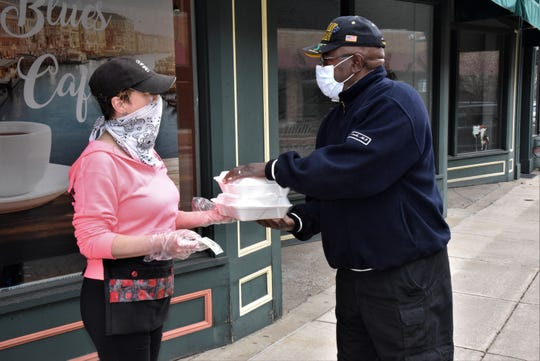 Kelly Vassallo of Barista Blue Cafe does curbside service for Danny Moss outside the restaurant at 91 West Michigan Ave. on Friday, April 24, 2020.