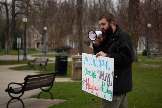 Adam Heikkila from Bedford protests Gov. Gretchen Whitmer's stay-at-home order at the traffic circle in downtown Marshall. Mich. on Friday, April 24, 2020.