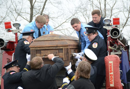 Firefighters lift the casket of Allen Seedorff from the back of a fire engine before his burial on Friday.