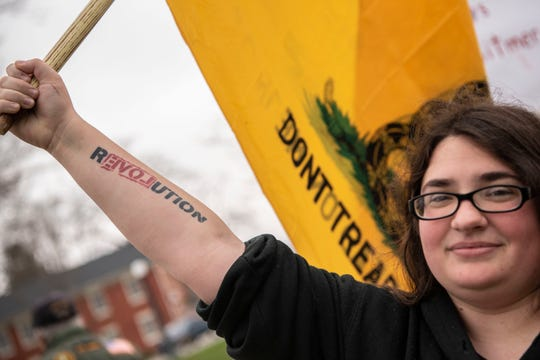 Michelle Gregorie protests Gov. Gretchen Whitmer's stay-at-home order at the traffic circle in downtown Marshall. Mich. on Friday, April 24, 2020.