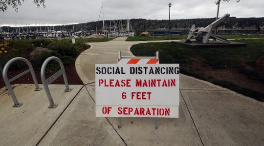 A sign reminding people of social distancing measures stands at an entrance to the Poulsbo Waterfront on April 21, 2020.
