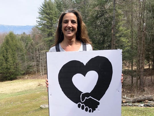 Liz Subin, one of four board members for nonprofit Heart & Soul of Essex, poses at her home with the group's logo on April 24, 2020. Subin, along with Lori Houghton, Gabrielle Smith and Sue McCormack, spearheaded a local effort to raise emergency funds for cash-strapped residents of Essex and Westford during the coronavirus pandemic.