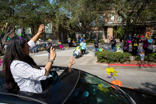 People wave to family members at Alameda Oaks Nursing Center as they take part in a parade on Friday, April 24, 2020. Alameda Oaks held  a parade for its residents, who have not had visitors since the start of the COVID-19 outbreak.