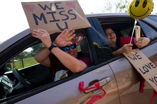 People wave to their family members at the Alameda Oaks nursing center as they take part in a parade on Friday, Aril 24, 2020. Alameda Oaks nursing center hosted a parade for its residents, who have not had visitors since the start of the COVID-19 outbreak.