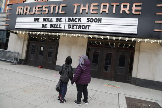 """Flossie Norton, 68, of Detroit checks out the Majestic Theatre marquee as she and her grandson Michael Morgan, 10, of Detroit get out for some fresh air. """"The streets are naked"""" said Norton. f"""