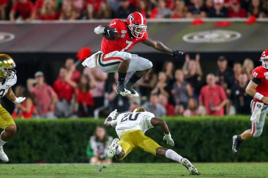 Georgia running back D'Andre Swift hurdles Notre Dame cornerback Shaun Crawford in the third quarter at Sanford Stadium, Sept. 21, 2019 in Athens, Ga.