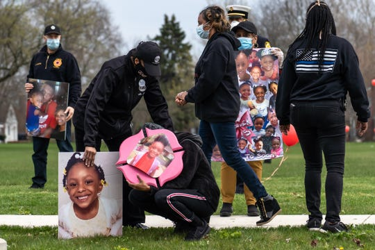 A woman crouches while emotional as Detroit Police Department officer LaVondria Herbert walks past .