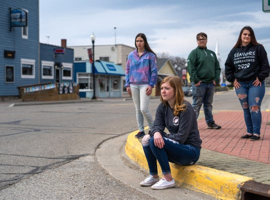 "(left to right) Caseville High School seniors Louise Barrios, Bayley McIlhargie, Tanner Gast and Cortney Moody sit along Port Austin Rd. in downtown Caseville on Wednesday, April 22, 2020. ""I'm not really sad I'm just kind of disappointed. I feel like if I look back on it in ten years I'l probably joke about it,"" McIlhargie said who is the Salutatorian for her class of 20 seniors whose senior year was cut short due to the COVID-19 pandemic. ""I'm not really worried about it personally. I'm more worried about my grandma and my older family members getting it. People were saying it was just like another flu so it didn't concern me until it started getting a little more serious."""