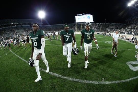 The Dowell brothers - David (6), Michael (7) and Andrew (5) walk off the field at Spartan Stadium after Michigan State's win over Utah State on Aug. 31, 2018, in East Lansing.