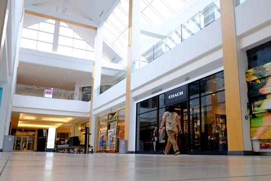 A visitor walks in an empty hallway at The Fashion Mall at Keystone in Indianapolis on March 18, 2020.