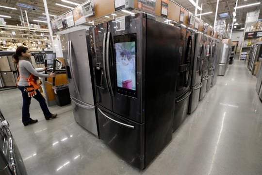 In this Jan. 27, 2020 photo a worker pushes a cart past refrigerators at a Home Depot store location in Boston. On Thursday, Feb. 27, the Commerce Department releases its January report on durable goods.