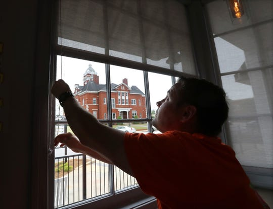 Brian Lambert, owner of Scoops, a coffee and sweets shop, opens up the windows of his business across the street from the Forsyth Courthouse as he gets ready to reopen in Forsyth, Ga.