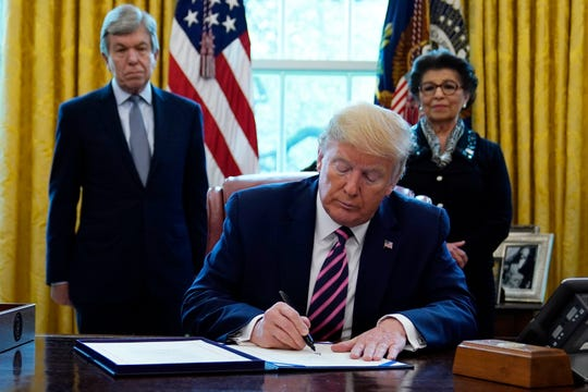 President Donald Trump signs a coronavirus aid package to direct funds to small businesses, hospitals, and testing, in the Oval Office of the White House on Friday in Washington. Sen. Roy Blunt, R-Mo., left, and Jovita Carranza, administrator of the Small Business Administration look on.