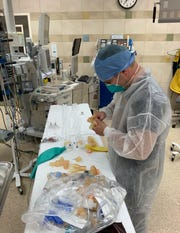 Otolaryngologist Dr. Kyle VanKoevering assembles an early prototype of the VentMI device in a laboratory at Michigan Medicine's C.S. Mott Children's Hospital in March 2020. The device allows more than one patient to safely use the same ventilator. Provided by Michigan Medicine, the University of Michigan's health system.
