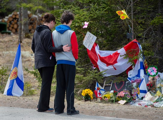 Visitors to a roadside memorial pay their respects in Portapique, Nova Scotia, on Friday, April 24, 2020.