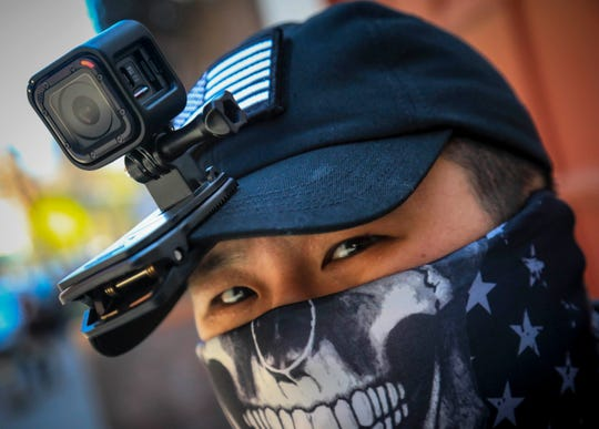 """Eddie Song a Korean American entrepreneur, arrives at his motorcycle storage garage wearing a video camera clipped to his cap and a face mask due to COVID-19 in East Village neighborhood of New York. """"I was assaulted a few months ago by someone who said that corona(virus) was created by Asians,"""" said Song."""