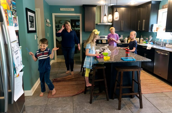 Porter Goebel, left, runs through the kitchen from his mom Holly, center, as his sisters occupy the island before they venturing outside to play in their backyard Friday morning, April 24, 2020. Holly Goebel says this is a typical morning in their household since the EVSC has gone to virtual learning.