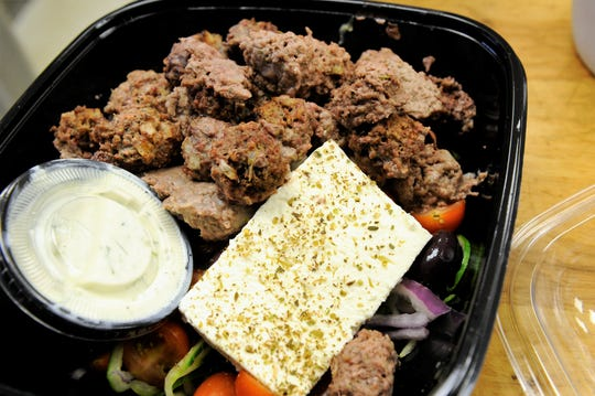 A chunky Greek salad with tomatoes, peppers, olives, onion, a slab of feta cheese, tzatziki and spiced gyro meatballs from Culinary Innovations.