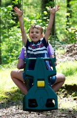 Porter Goebel, front, swings with his big sister Savannah as they play in their backyard Friday morning, April 24, 2020.