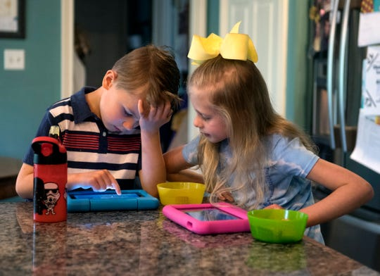 Porter Goebel, left, plays an educational game on an iPad as his twin sister Emmerson, right, checks his work Friday morning, April 23, 2020. Porter's mom Holly Goebel said her son's teachers have sent modified assignments to meet his special needs.