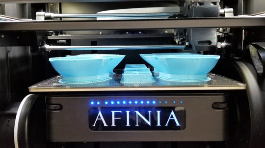 A 3D printer at Wabeno High School works to print a facemask. The machine will print for 13 hours  40 minutes to make four masks, or about 205 minutes each. About 65 grams of filament  are needed to print each mask, said WHS Fab Lab director Brian Van Eperen.