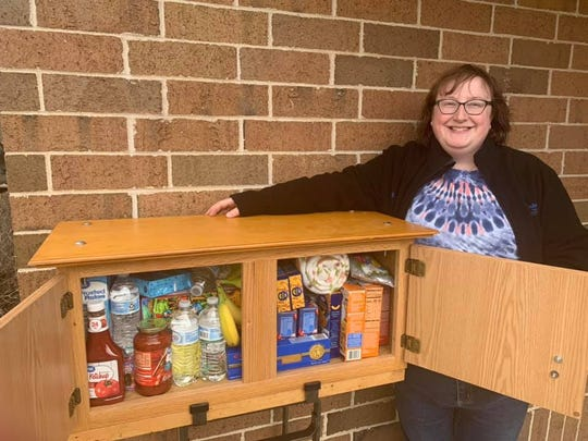 Door County Habitat for Humanity ReStore Manager Megan Dietz stands with the free pantry placed outside of Bay View Lutheran Church.