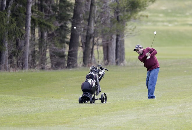A golfer hits the ball on the 18th hole of Hilly Haven Golf Course in De Pere on Friday. Courses in Wisconsin were allowed to reopen with certain restrictions under the updated safer-at-home order that was extended until at least May 26.