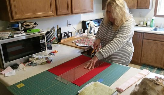 Charlie Brockman of Townsend cuts material for facemasks in her kitchen.