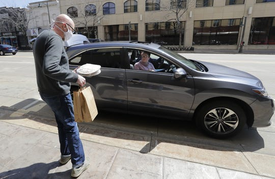 David Oliver, co-owner of Mondo! Wine Bar & Retail, brings a customer an order of pizza and bottles of wine for a curbside pickup Friday, April 24, 2020, in downtown Appleton. Oliver received a small business administration loan.
